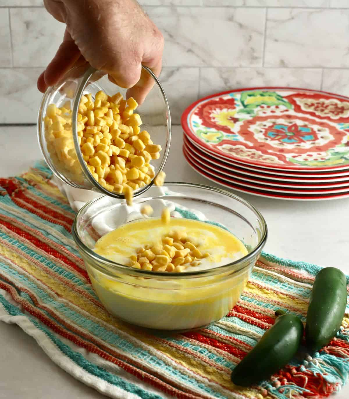 Pouring corn into a bowl with buttermilk and eggs.
