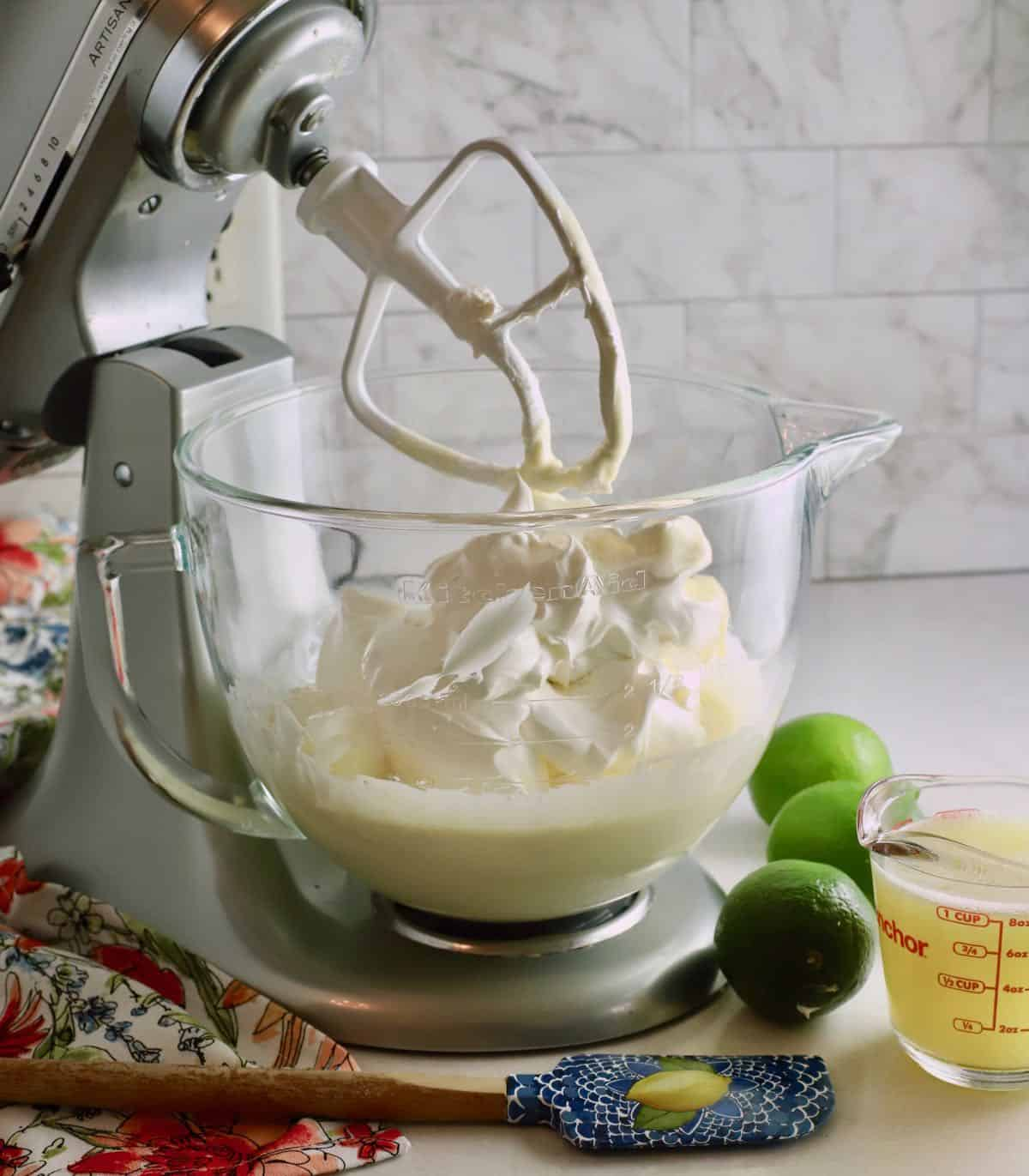 An electric mixer bowl full of cool whip and sweetened condensed milk.