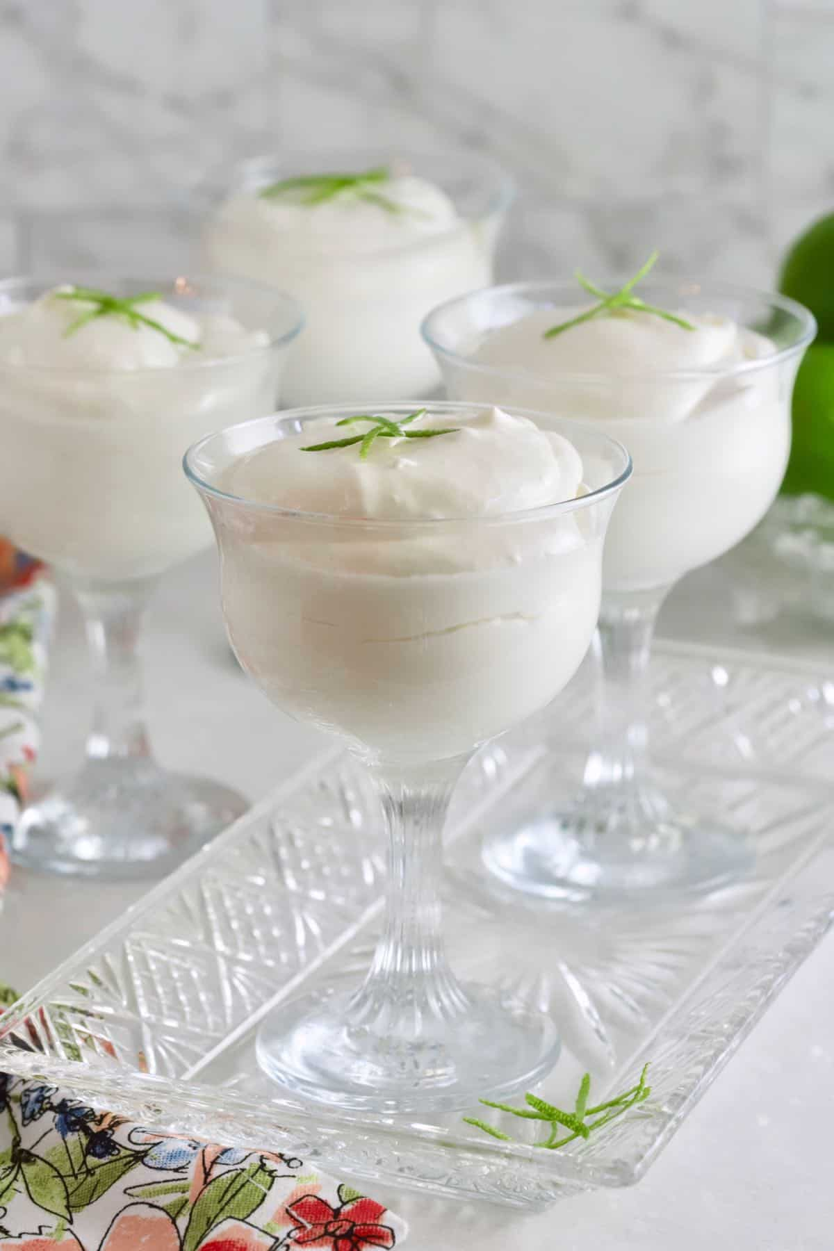 Key Lime Mouse in dessert glassed topped with strips of lime peel.