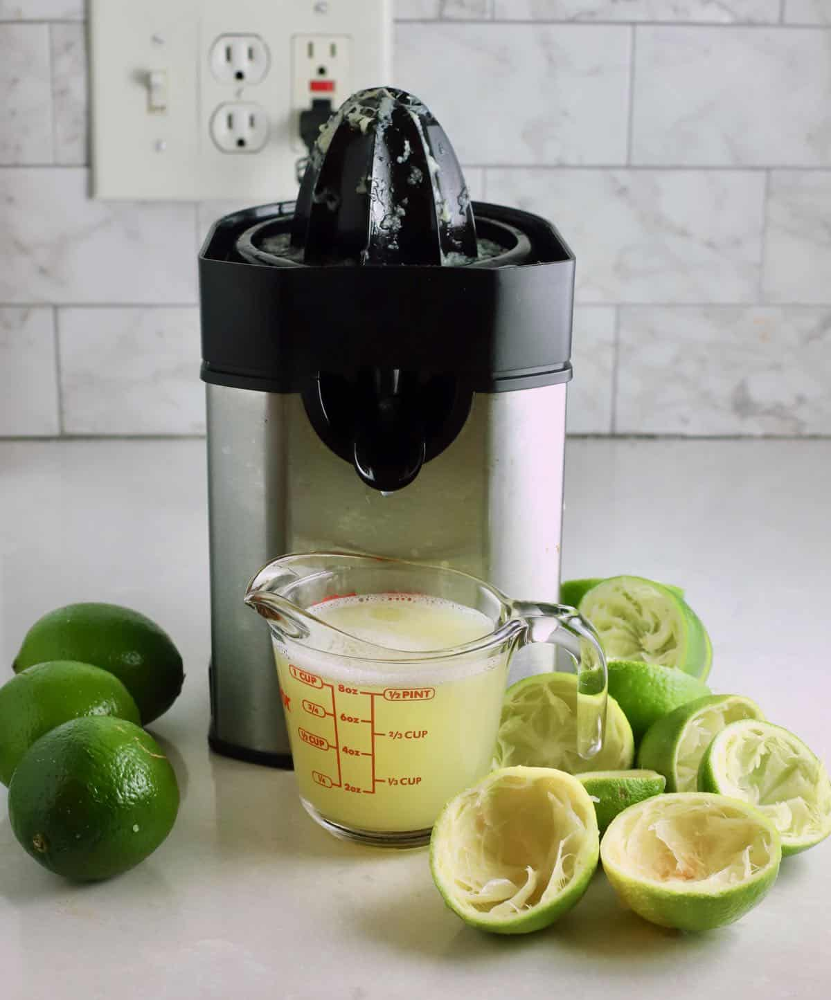 An electric juicer next to a measuring cup full of lime juice.