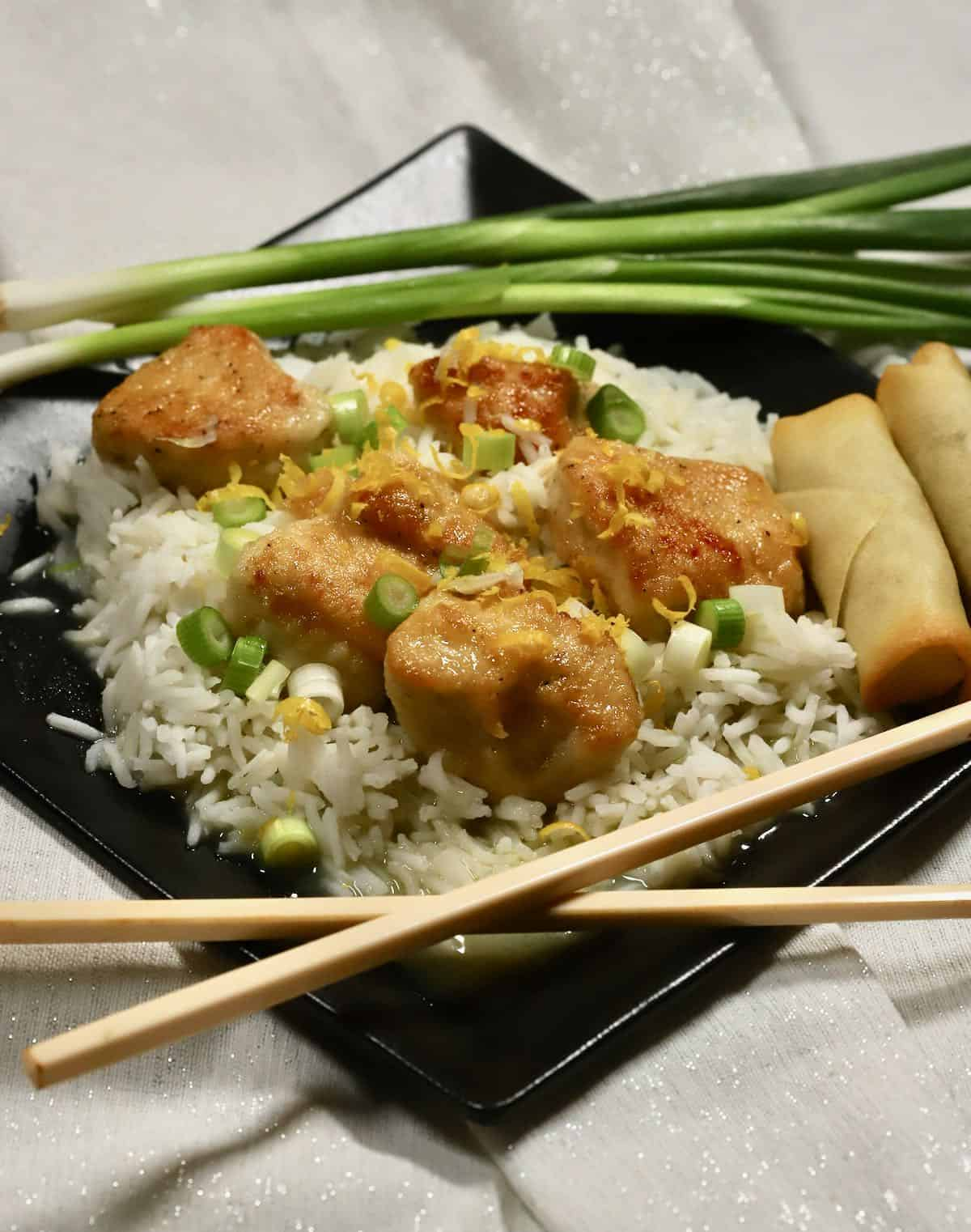 Pan-seared chicken pieces served over rice with scallions on top.