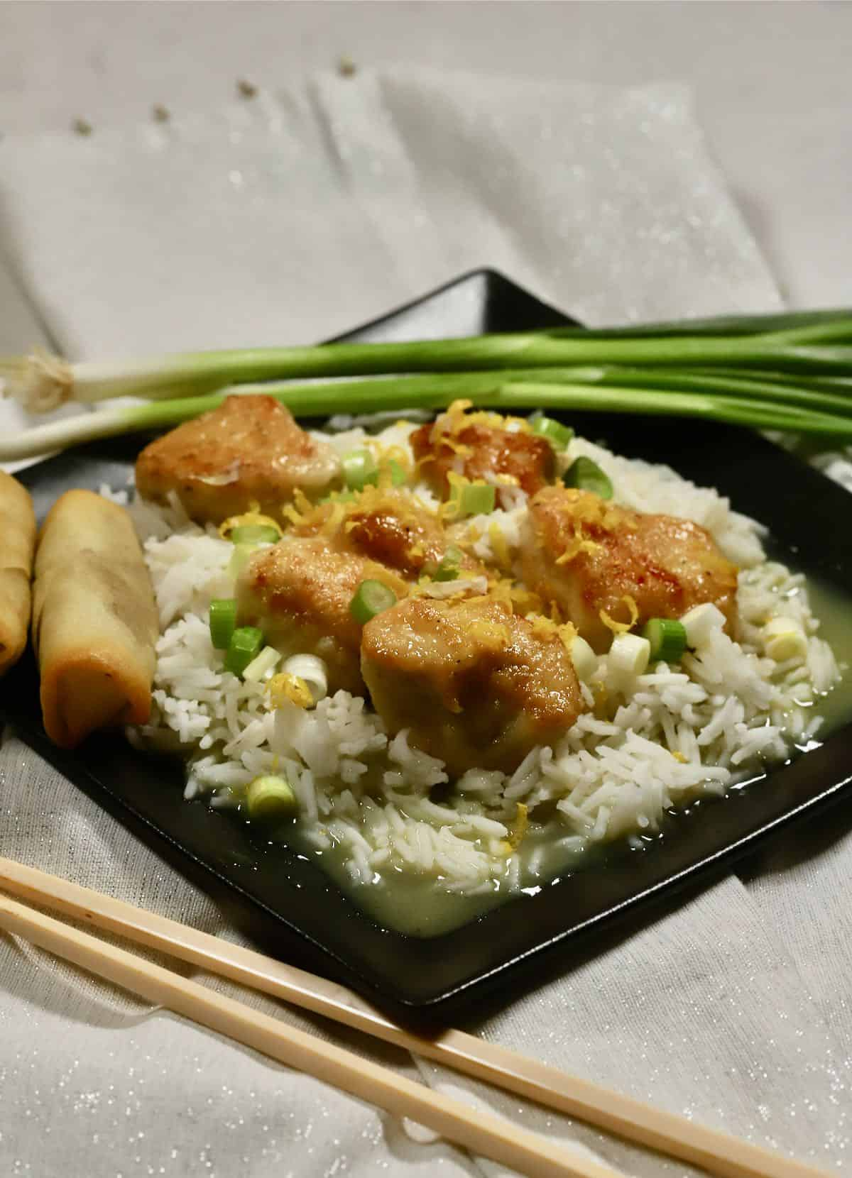 A black plate with rice topped with cooked pieces of chicken.