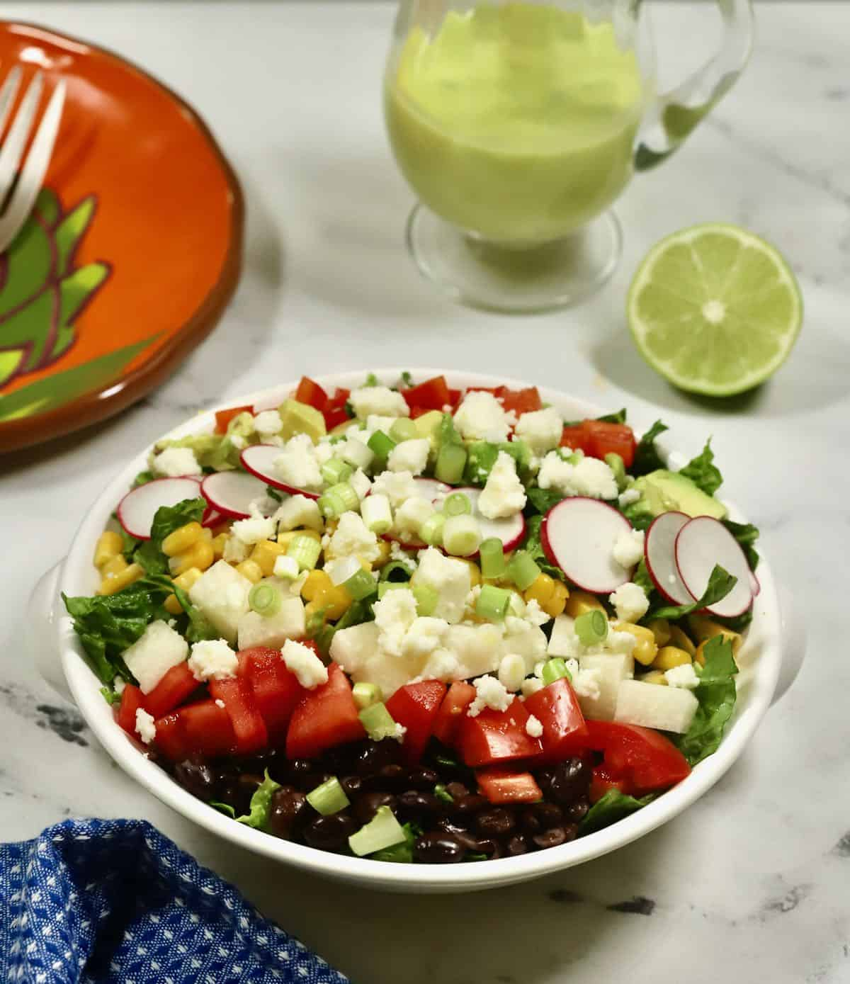 A large colorful salad with a small pitcher of dressing.