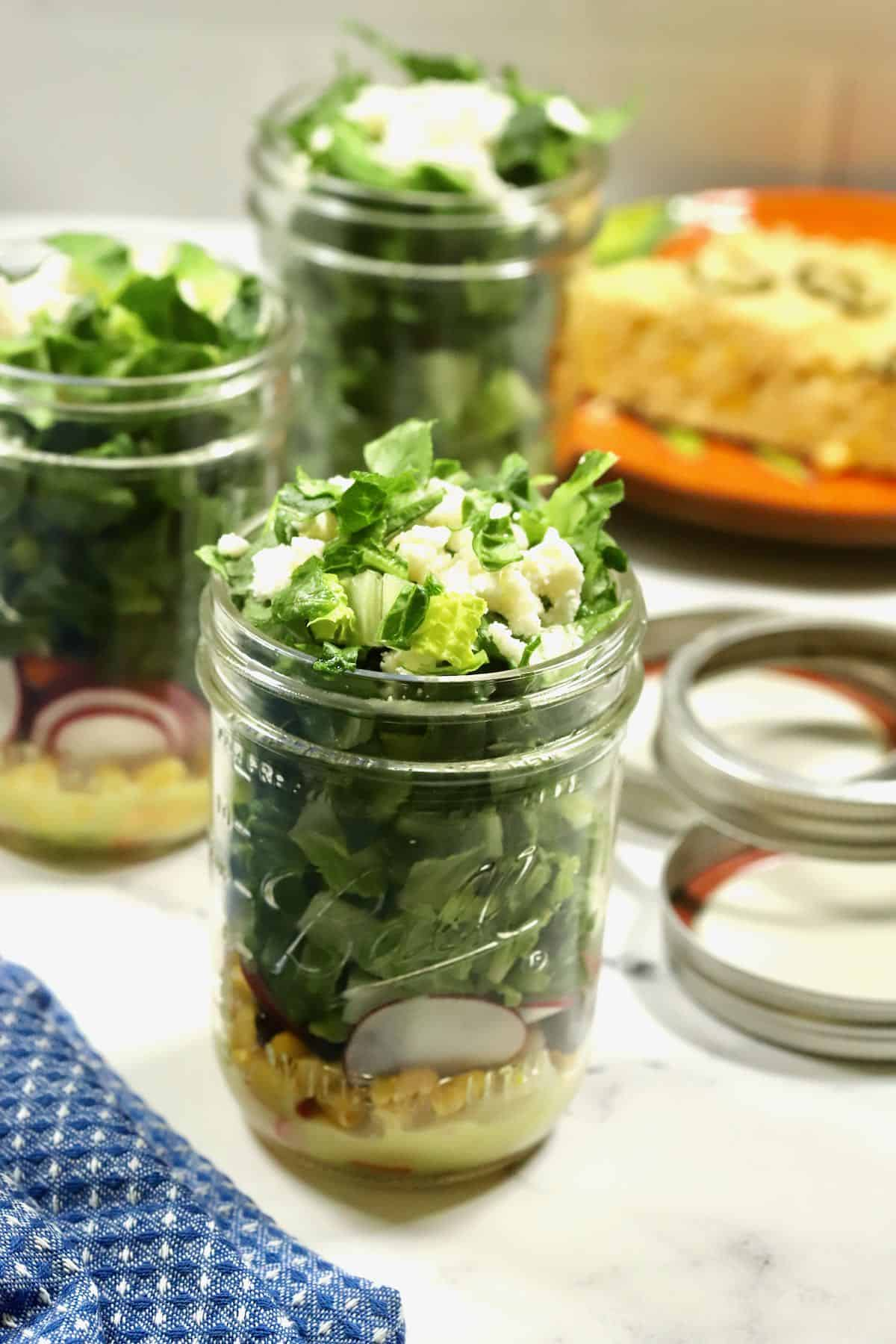A mason jar filled with salad and dressing.