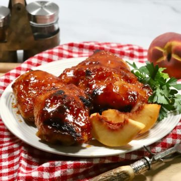A white plate with smoked chicken thighs on top of a red and white kitchen towel.