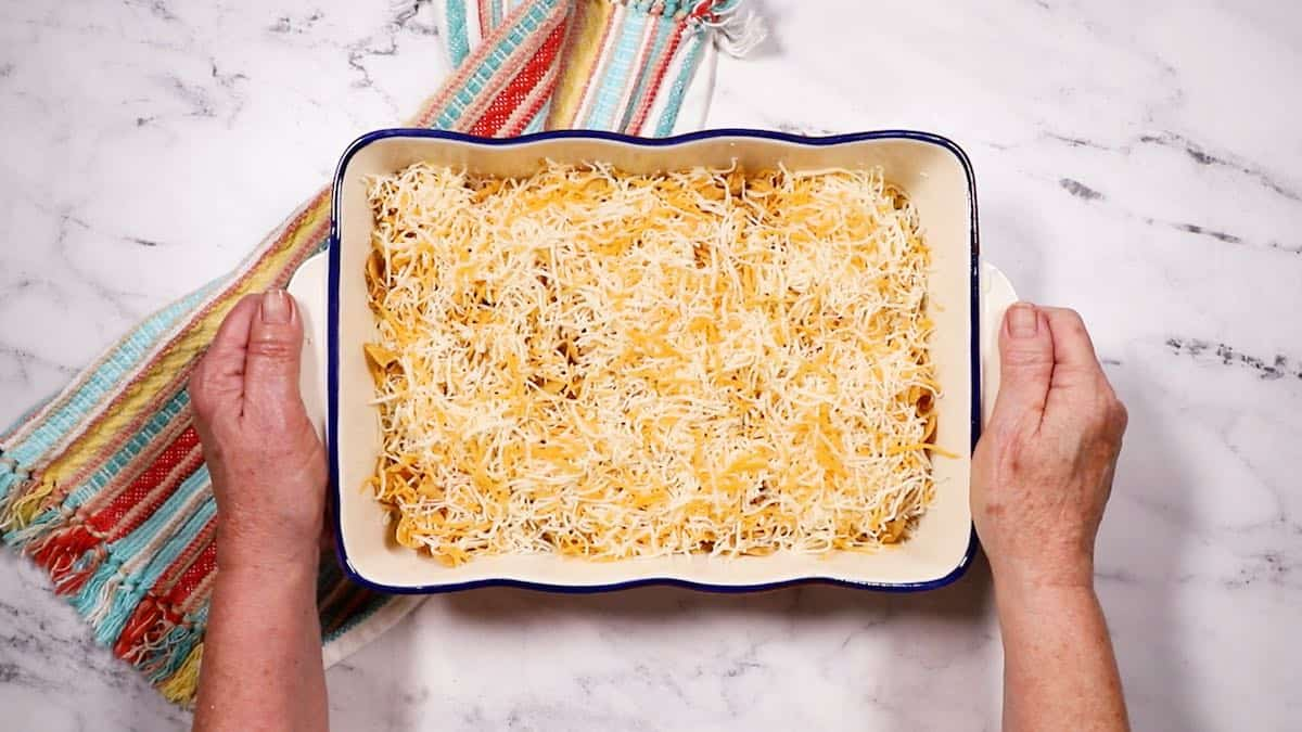 An unbaked taco casserole topped with cheese in a baking dish.