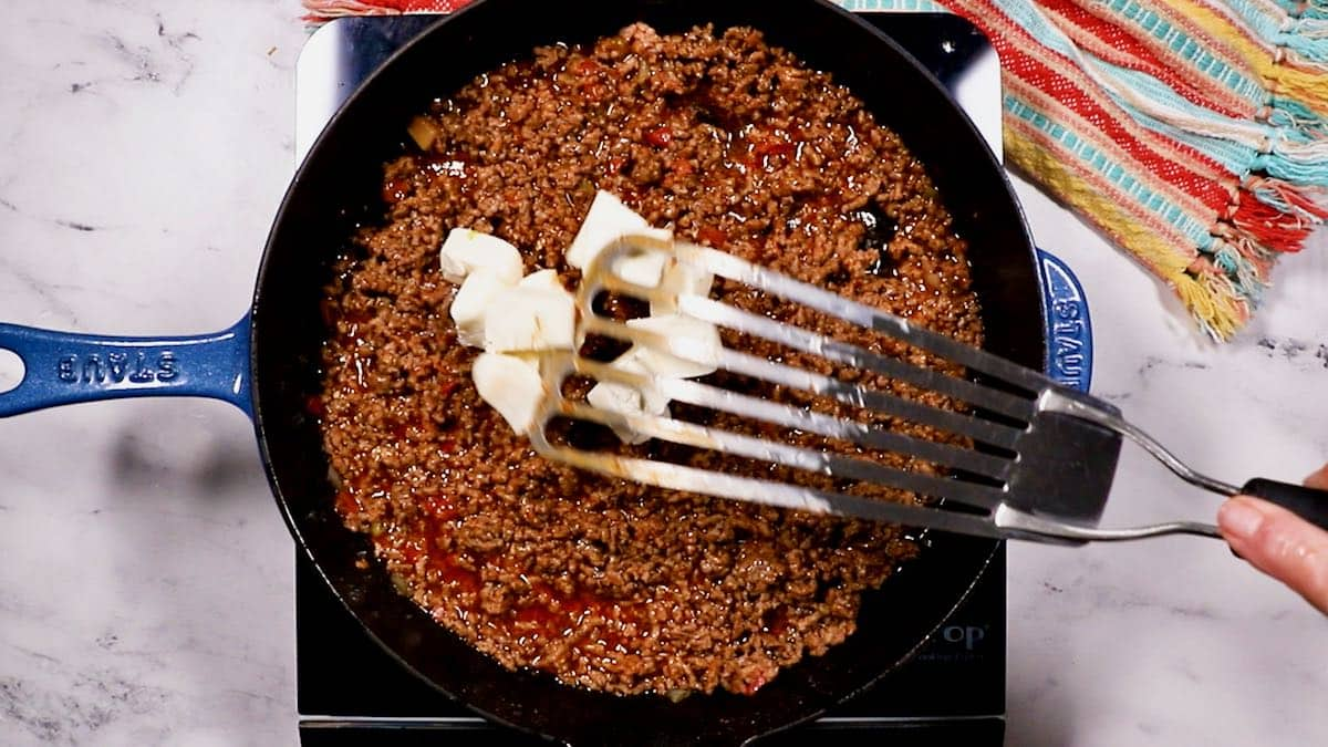 Adding cubes of cream cheese to taco meat cooking in a skillet.