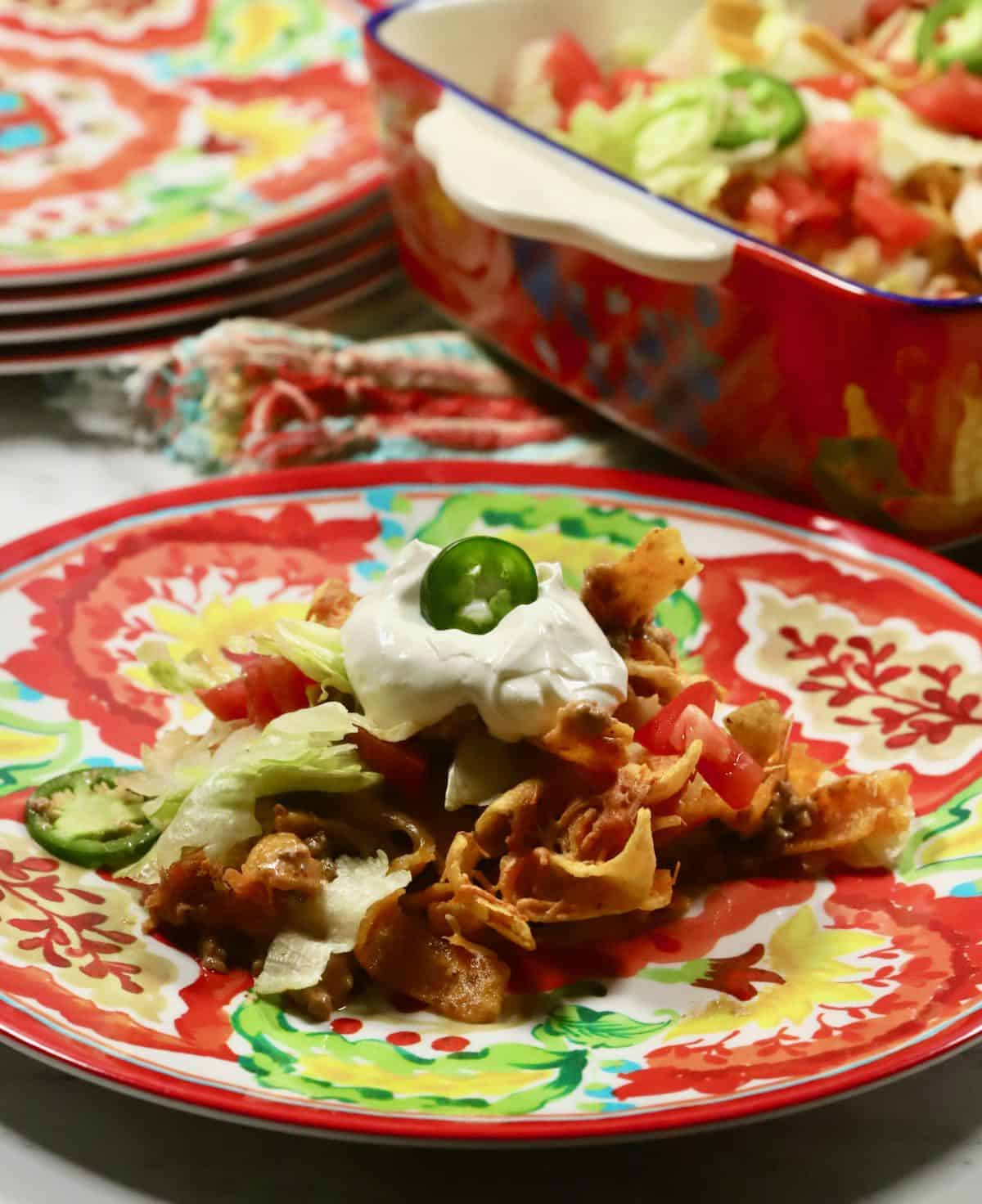 A brightly colored Mexican plate with a serving of taco casserole.