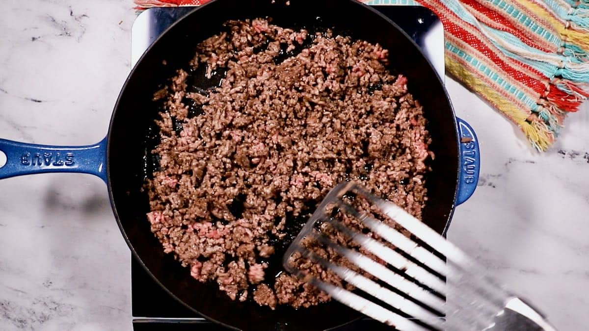 Cooking ground beef in a cast-iron skillet.