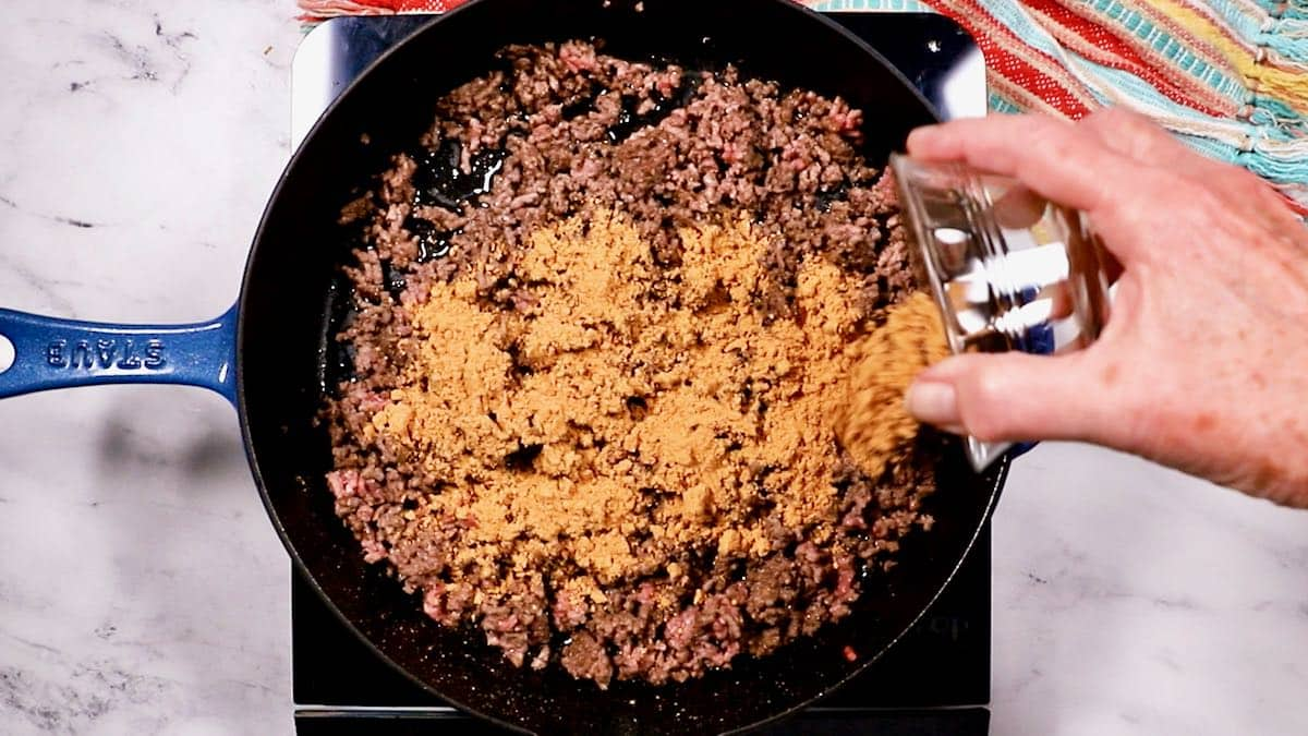 Adding dry taco seasoning to ground beef cooking in a skillet.
