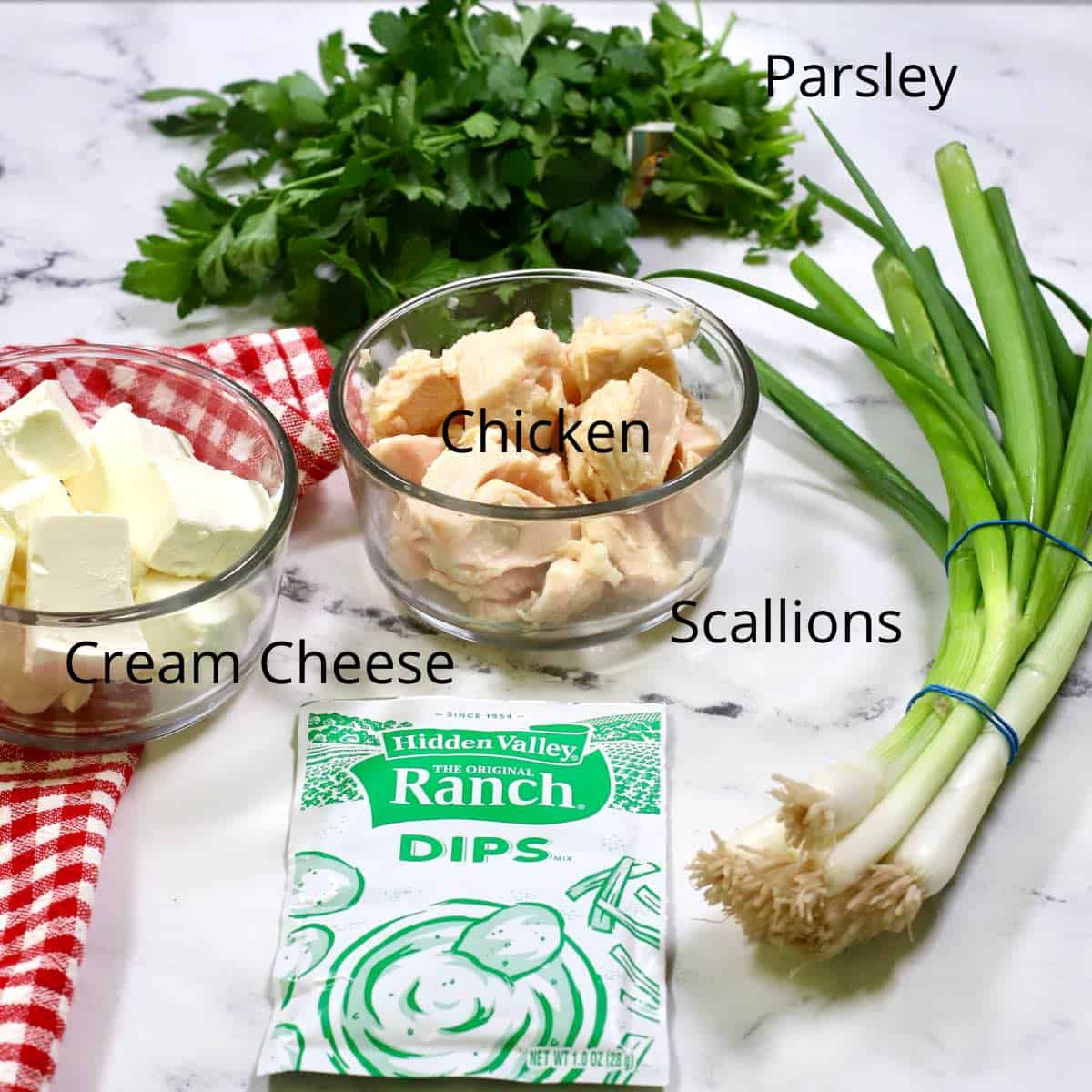 Ingredients for chicken ranch dip including cream cheese, scallions and chicken.