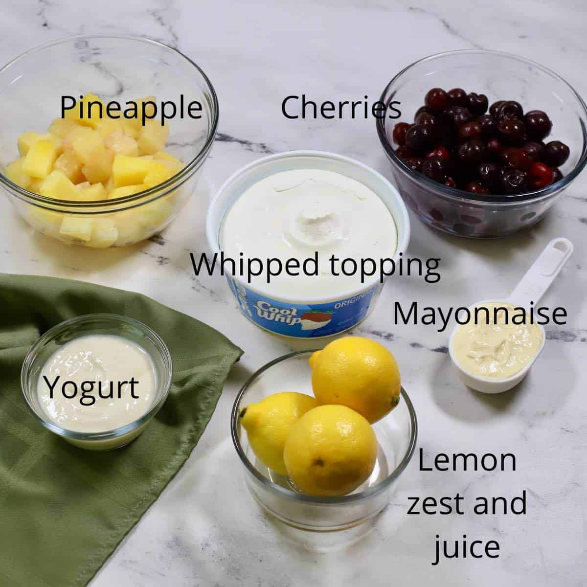 Ingredients for a frozen fruit salad including cherries and pineapple.