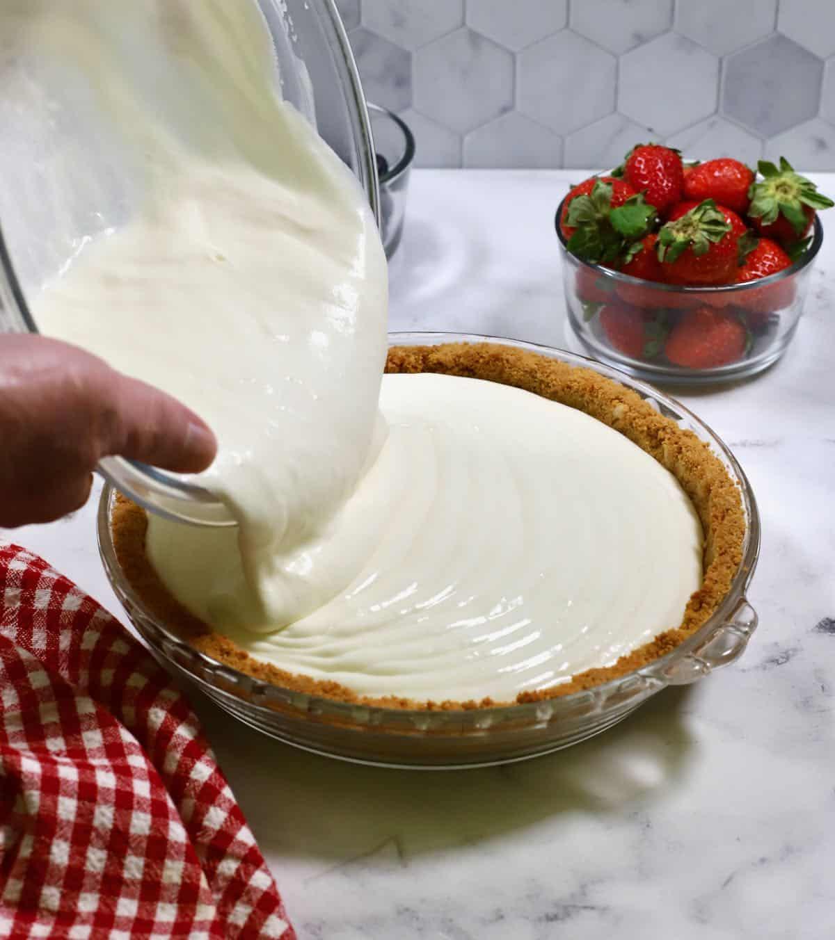 Pouring lemonade pie filling into a graham cracker crust.