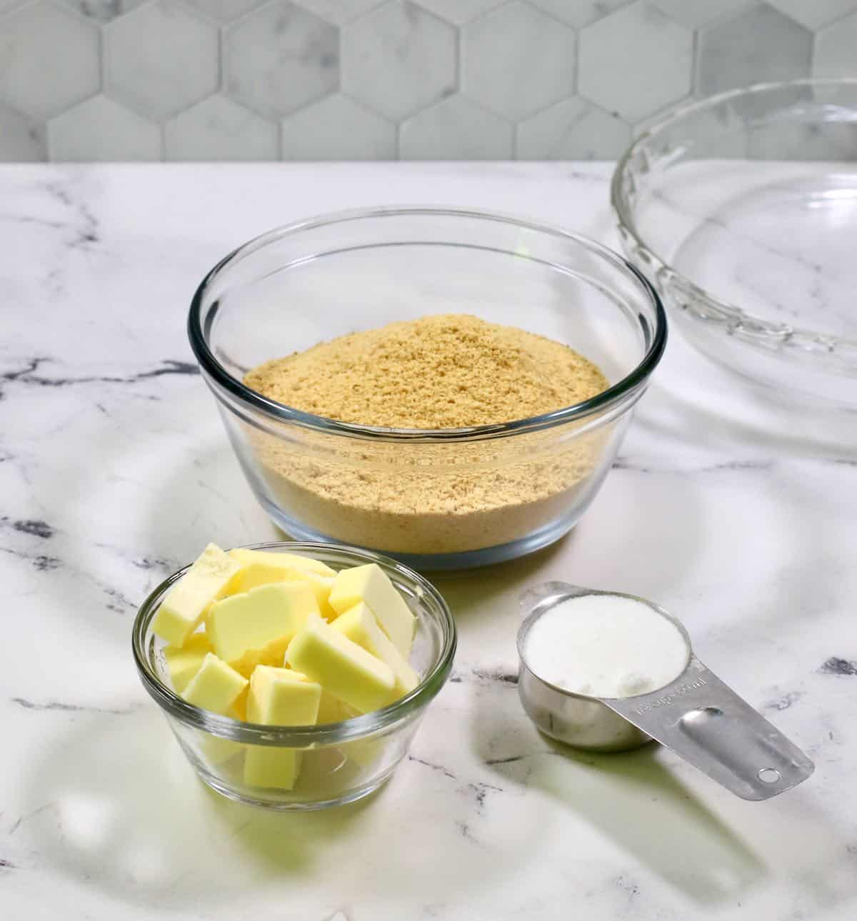 A bowl of graham cracker crumbs, butter, and sugar on a countertop.