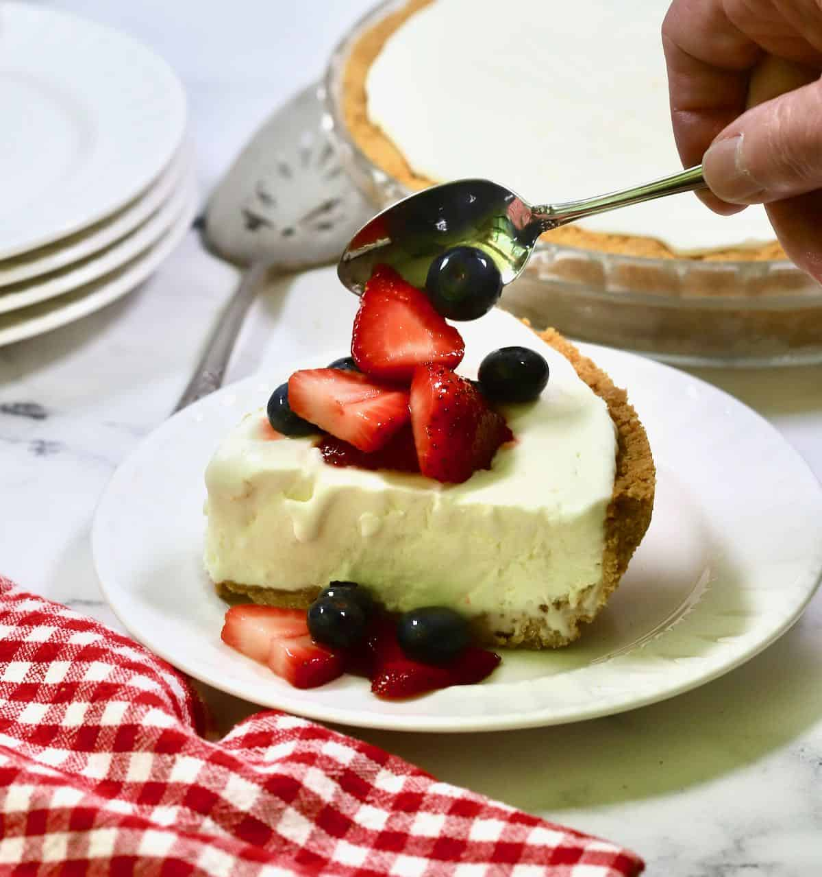 A slice of frozen lemonade pie topped with a spoonful of macerated berries.