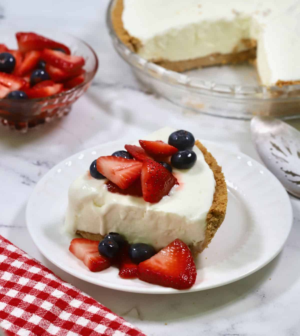 A slice of frozen lemonade pie topped with macerated berries.