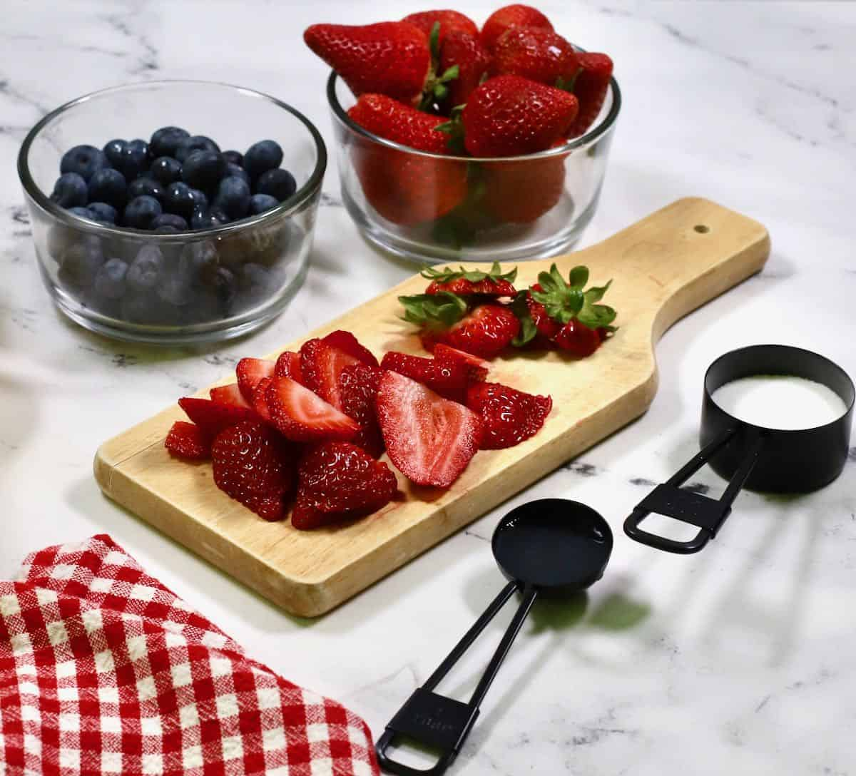 Fresh sliced strawberries and blueberries on a wooden cutting board.