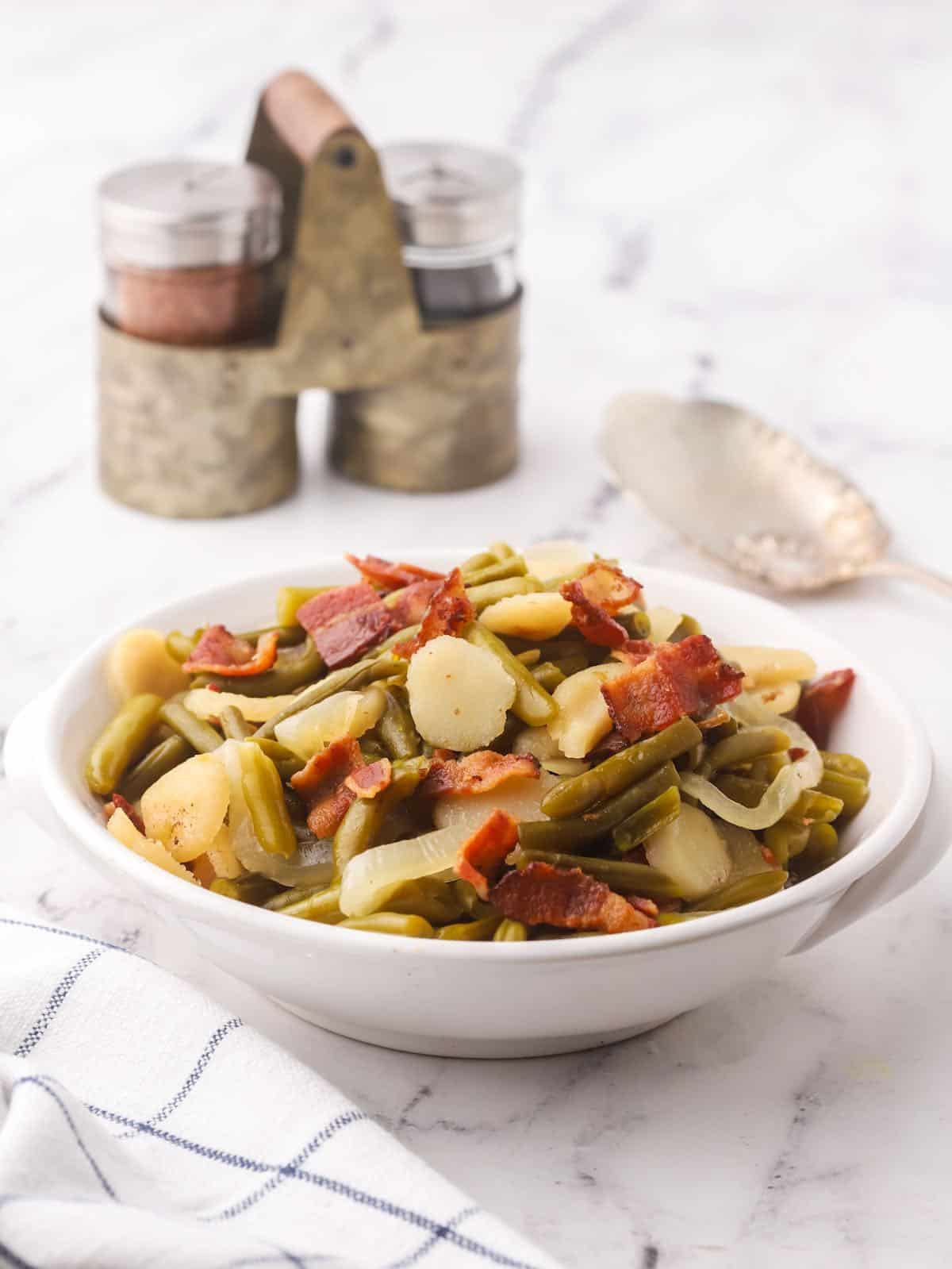 A white serving ddish with sweet and sour green beans topped with crumbled bacon.