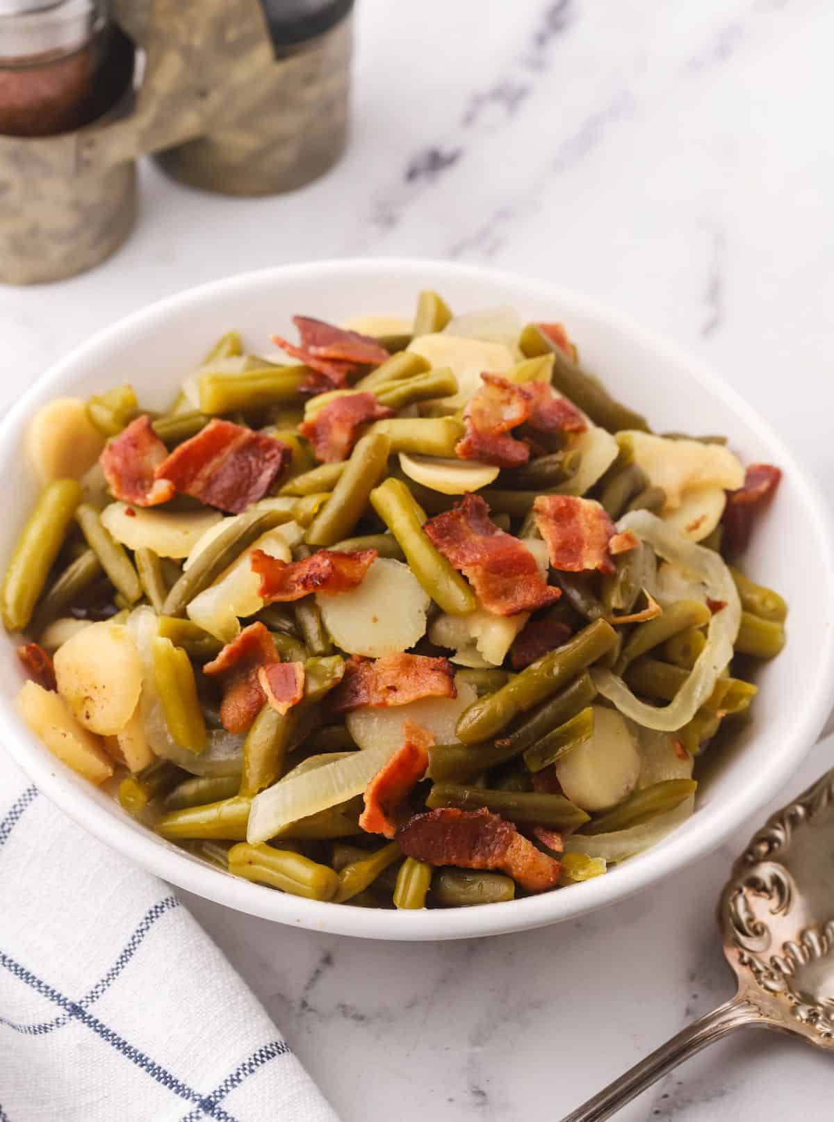 Sweet and sour green beans topped with bacon in a white serving bowl.