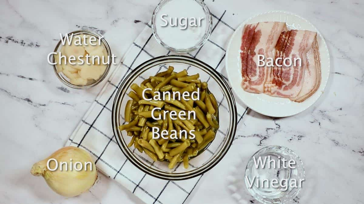 A bowl of canned green beans, bacon, onion and other ingredients for sweet and sour green beans.