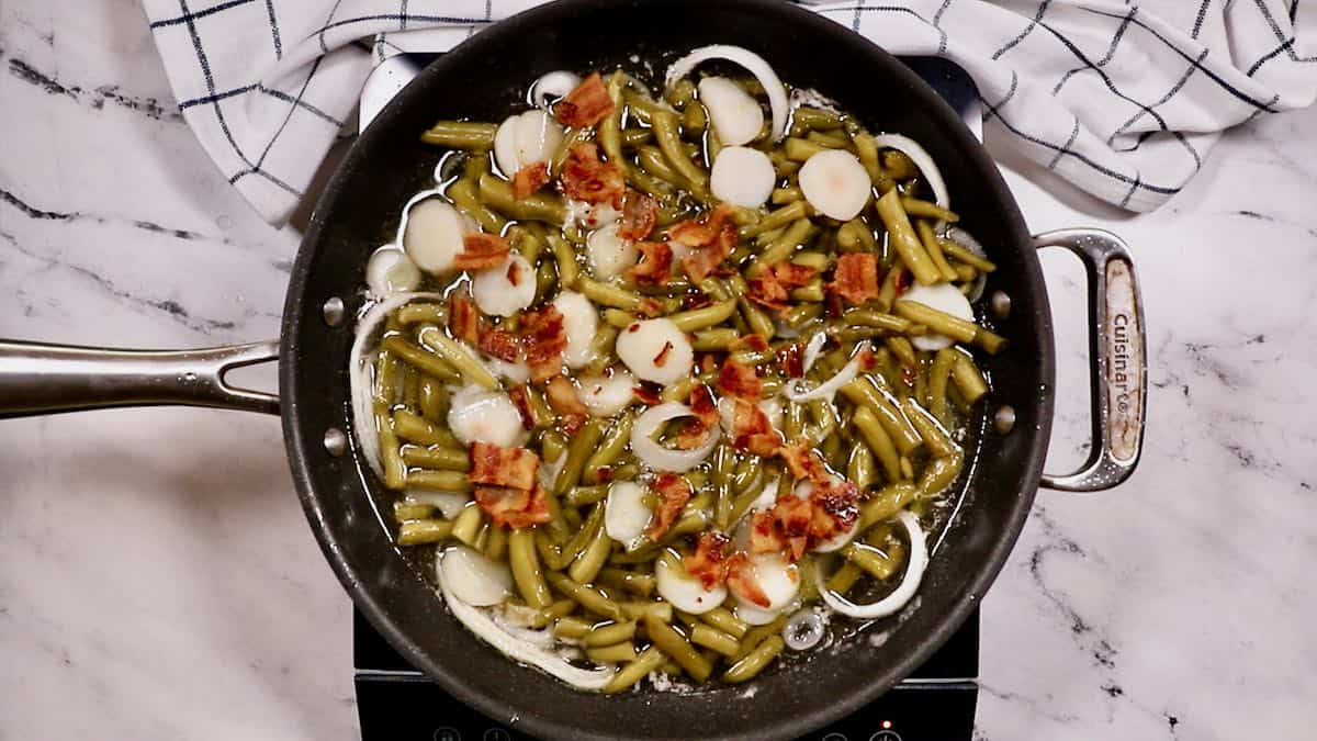 Sweet and sour green beans cooking in a skillet topped with bacon.