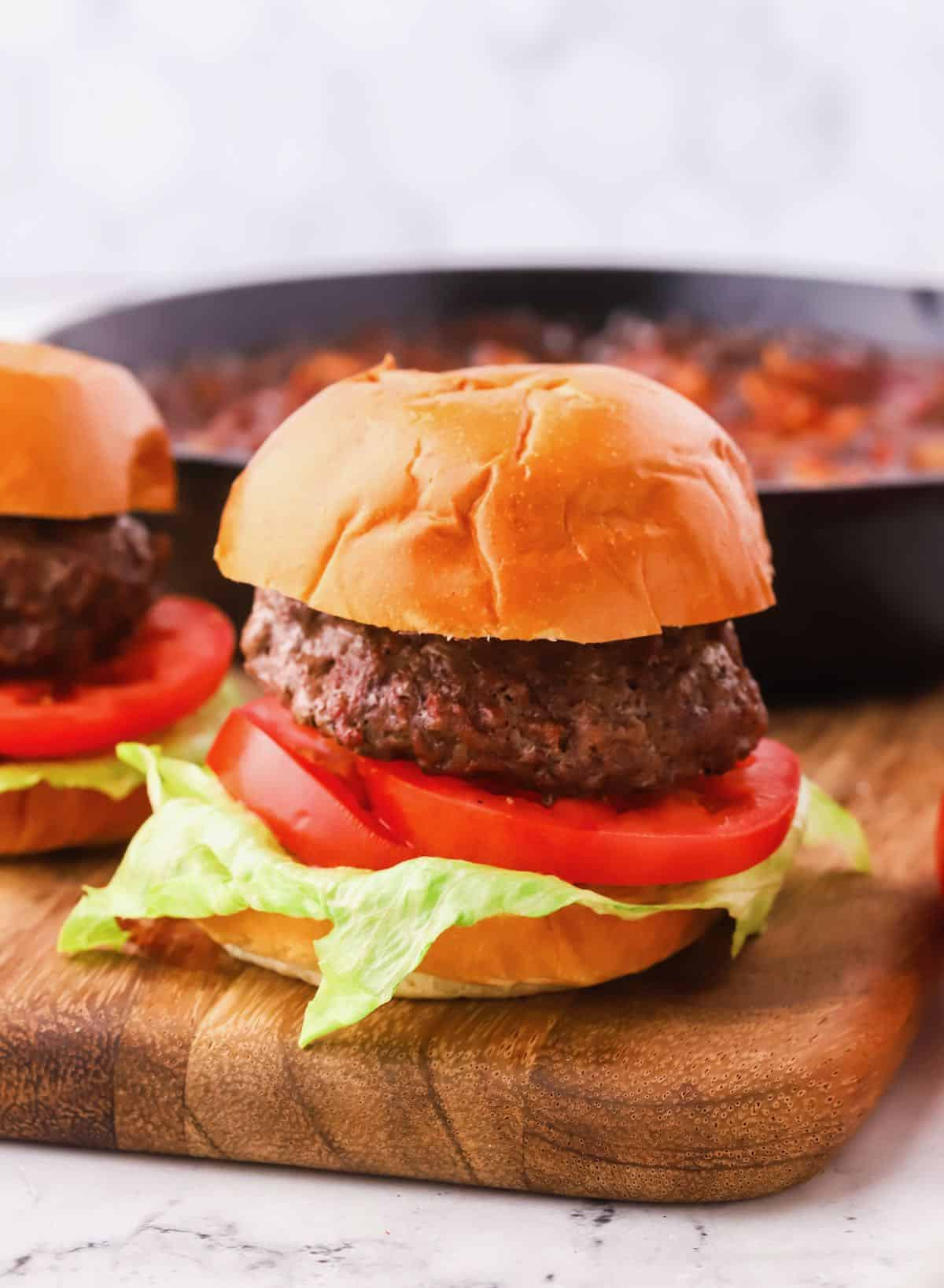 A hamburger on a bun with lettuce and tomato.