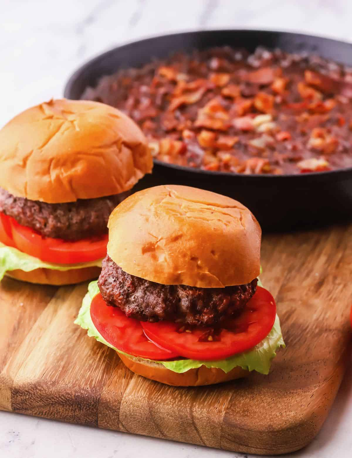 Two burgers on a wooden cutting board with a pan of baked beans.