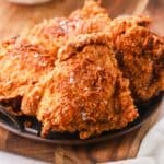Four pieces of fried chicken on a plate.