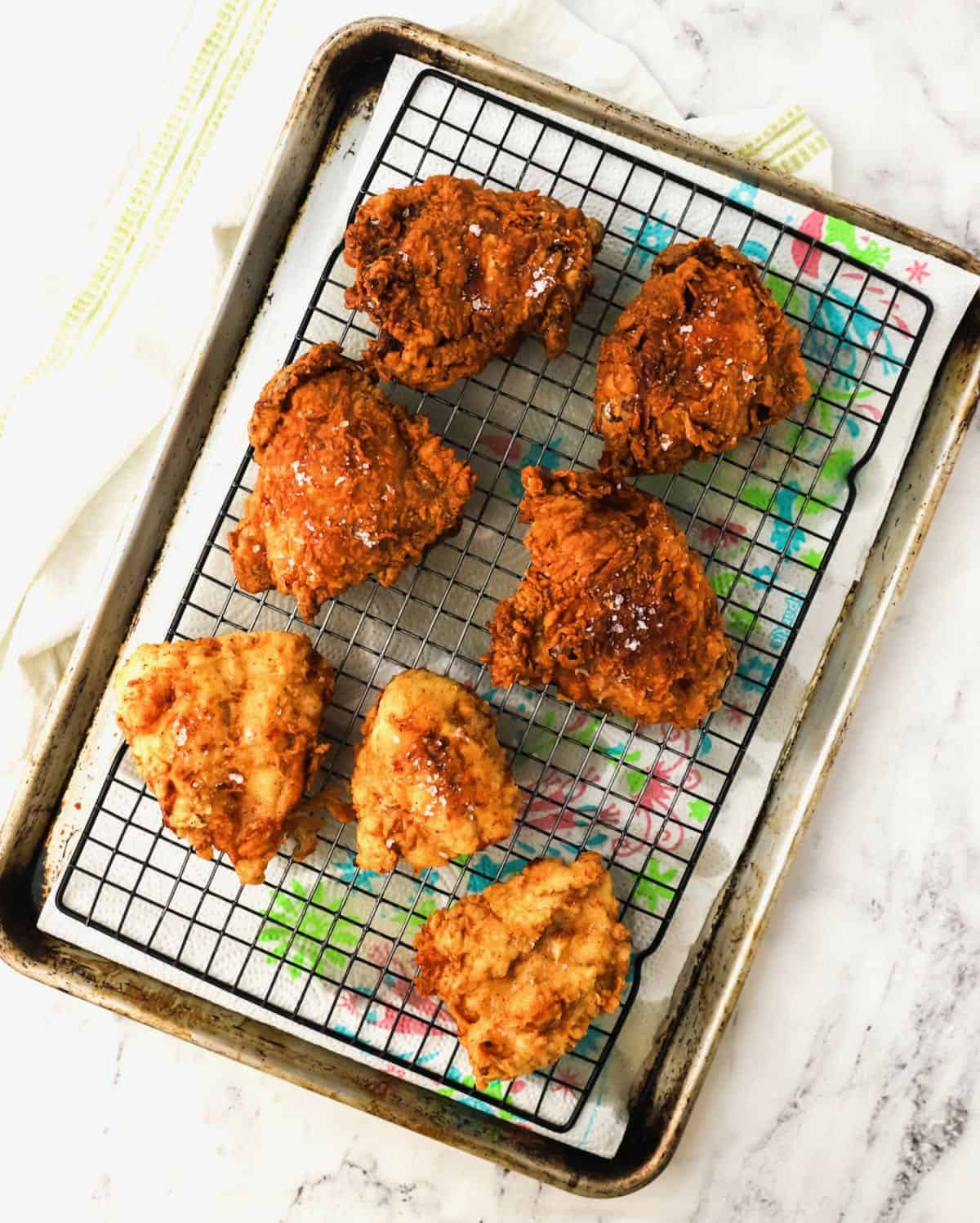 Fried chicken draining on a wire rack.