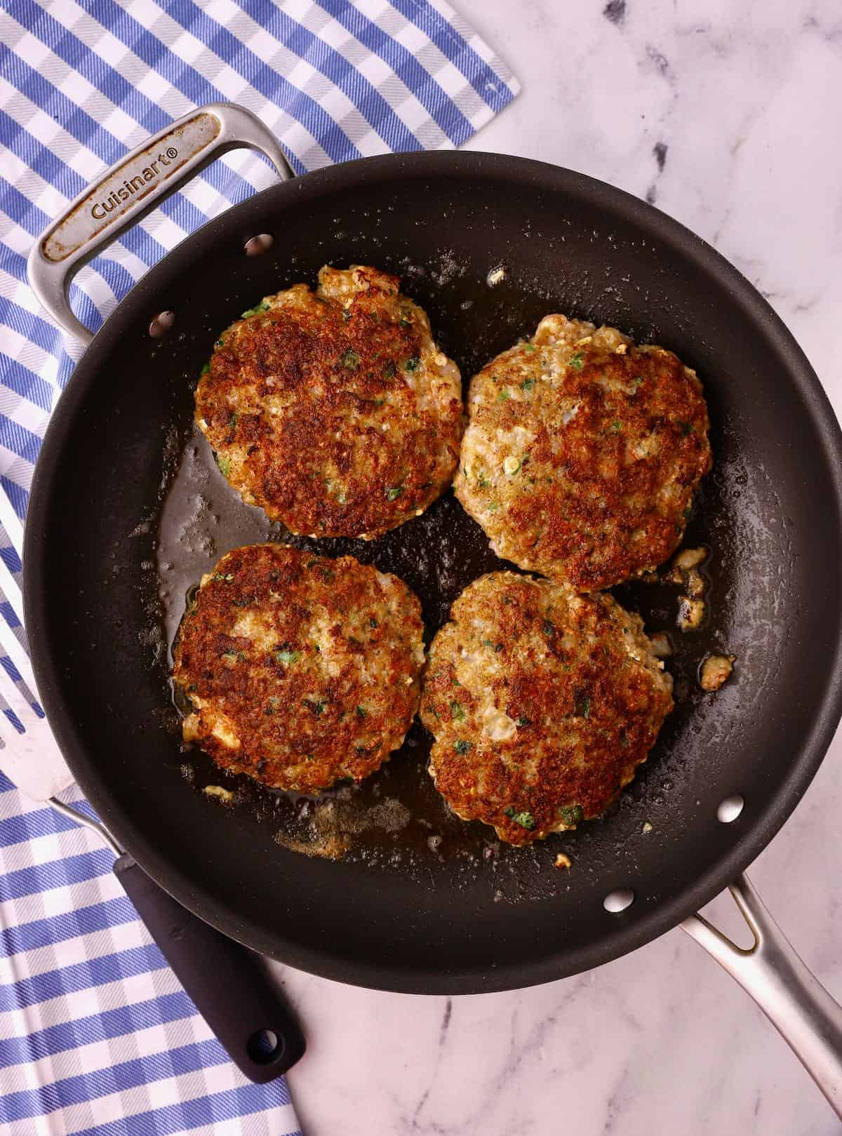 Four shrimp burgers cooking in a skillet.