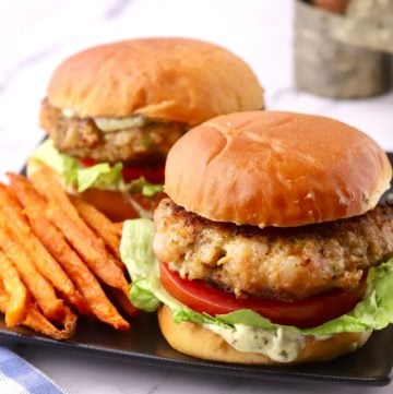 Two shrimp burgers with sweet potato fries.