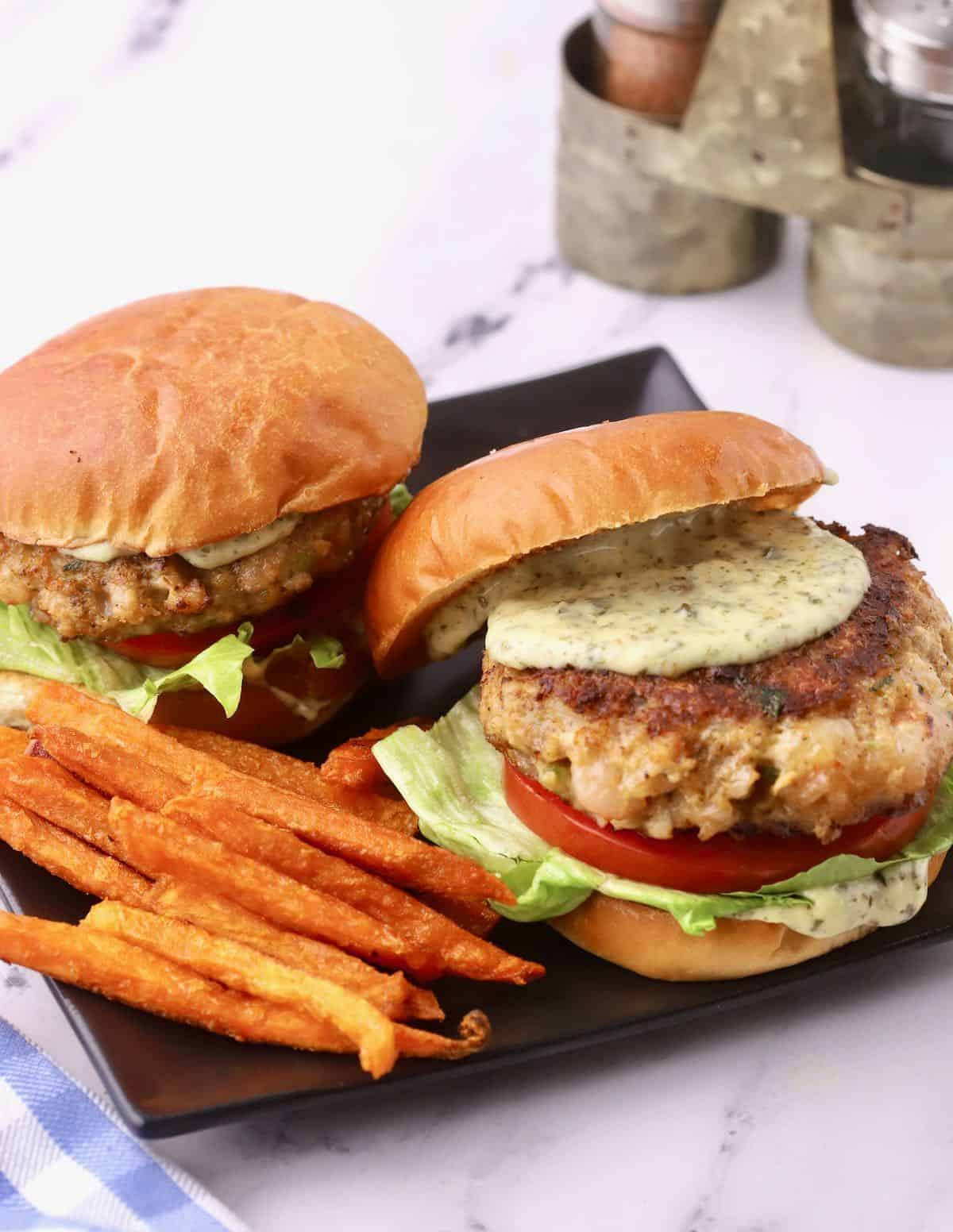 Two shrimp burgers on a black plate.