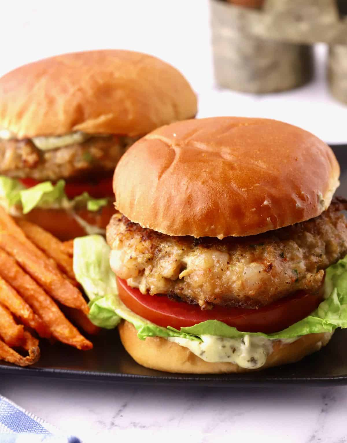 Two shrimp burgers with lettuce and tomato.
