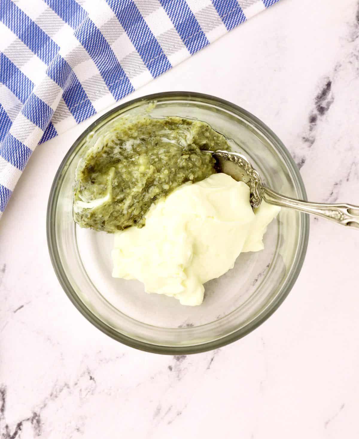 Basil pesto and mayonnaise in a small glass dish.