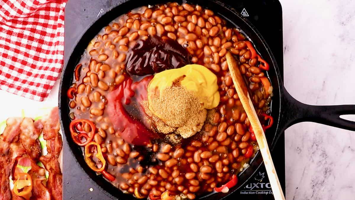 A skillet full of baked beans plus mustard, ketchup, and BBQ sauce.