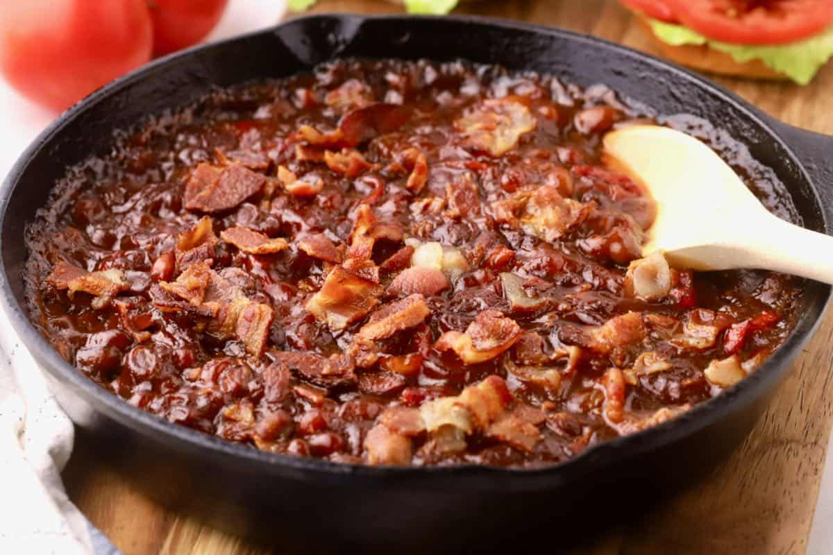 Smoked baked beans in a cast-iron skillet with a wooden spoon.
