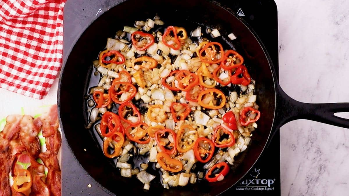 Onions and peppers cooking in a cast-iron-skillet.