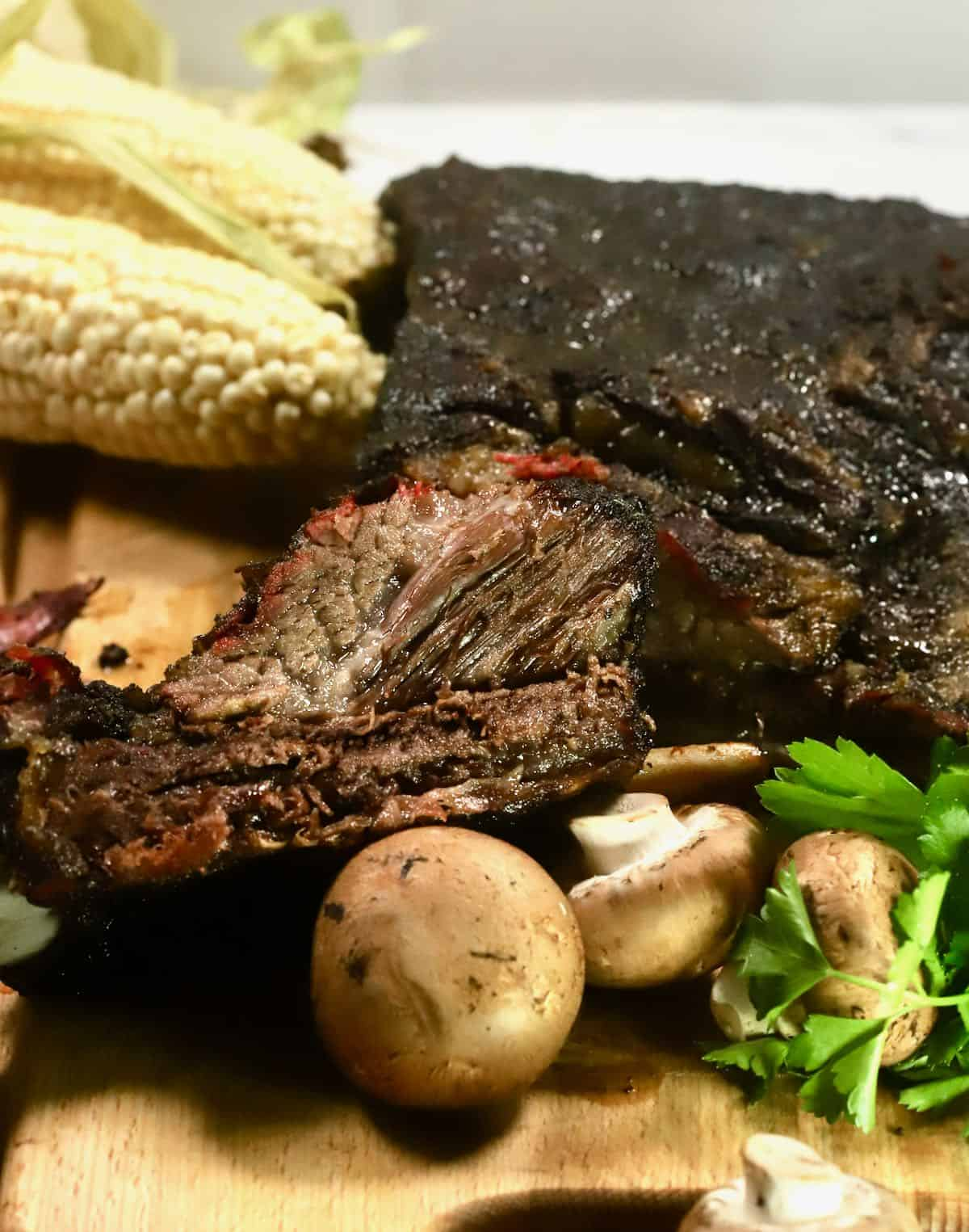 Smoked Beef Short Ribs on a cutting board with corn.