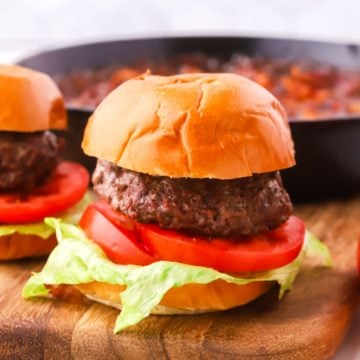 A burger with lettuce and tomato on a cutting board.