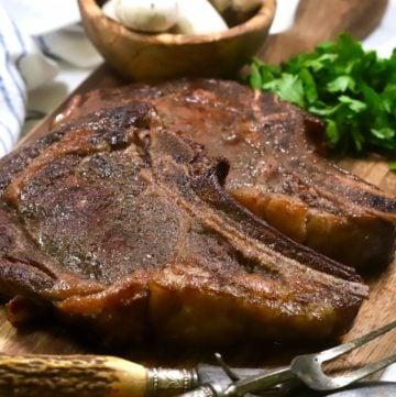 Two smoked ribeye steaks on a cutting board.