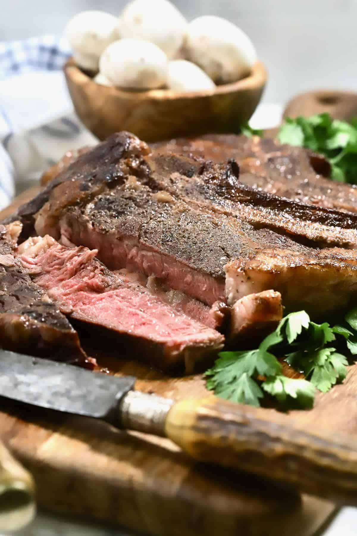 A ribeye steak sliced on a cutting board.