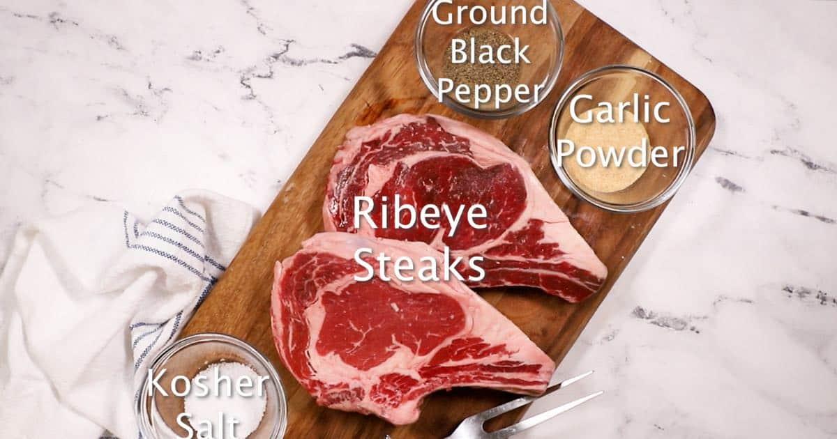 Two steaks, salt, pepper, and garlic powder on a cutting board.