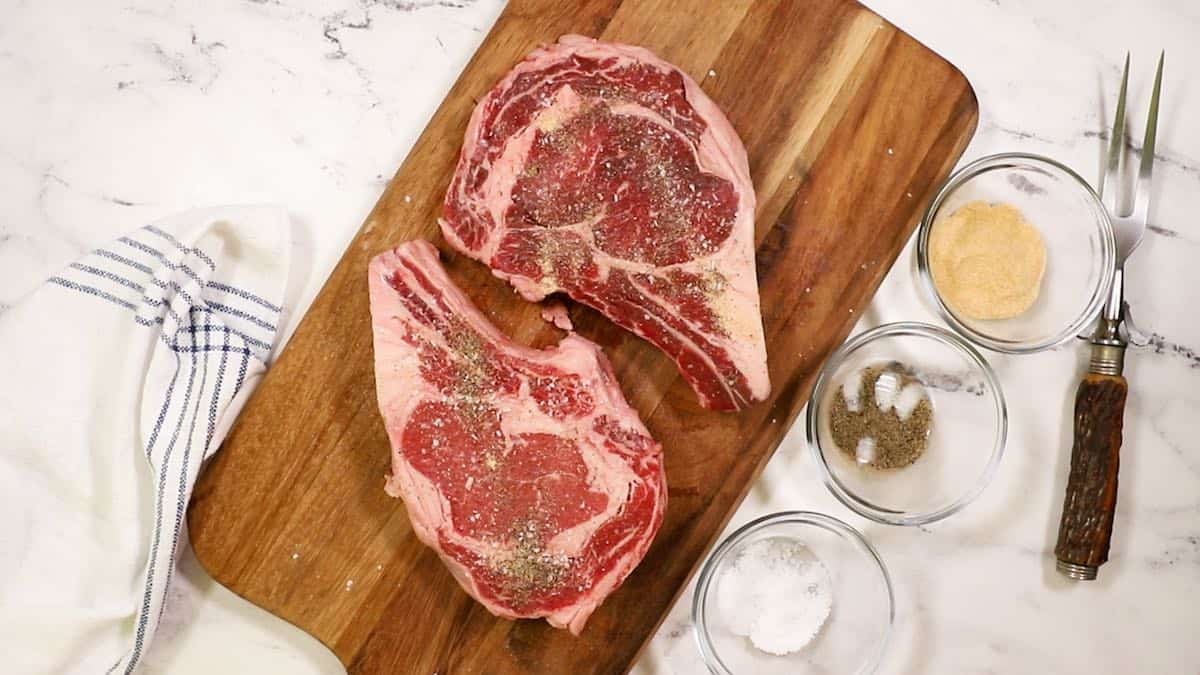 Two raw ribeye steaks on a cutting board topped with salt and pepper.  on