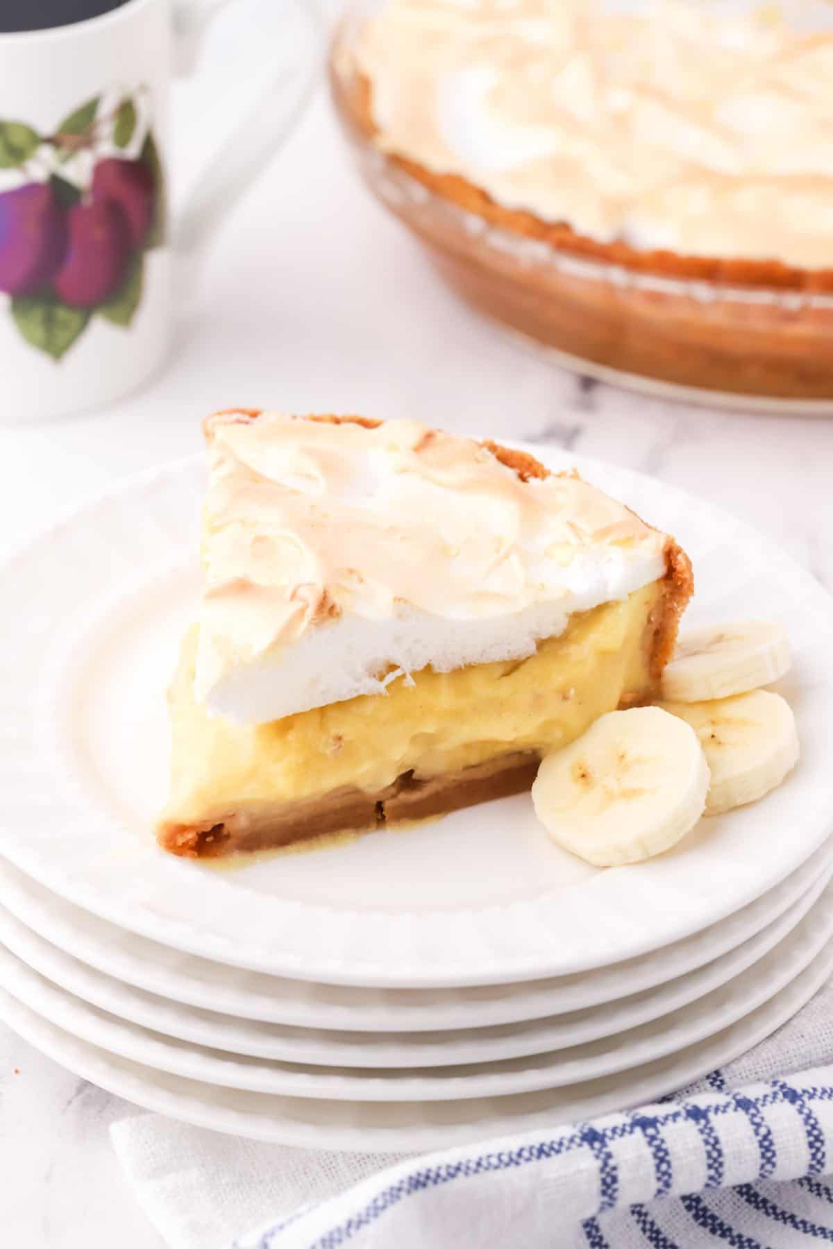 A slice of banana pudding pie on a white plate.