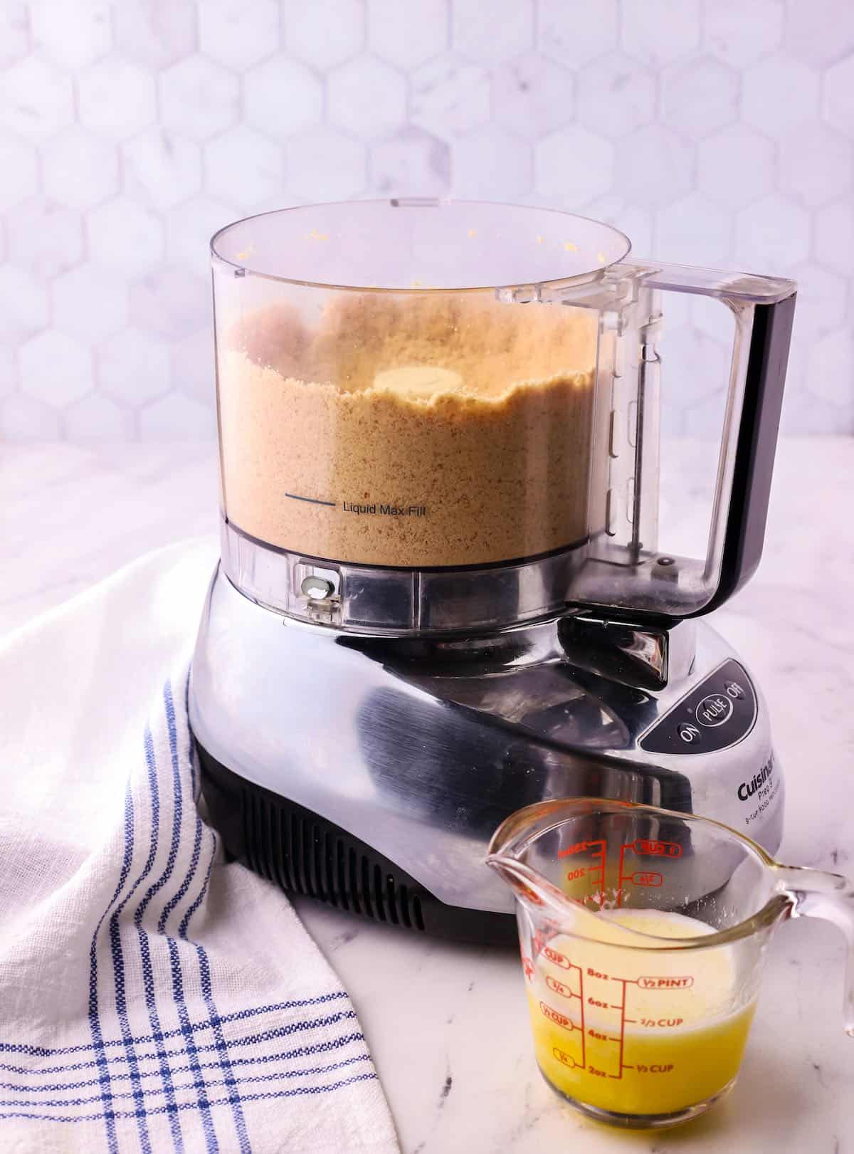 A food processor with crushed vanilla wafers.