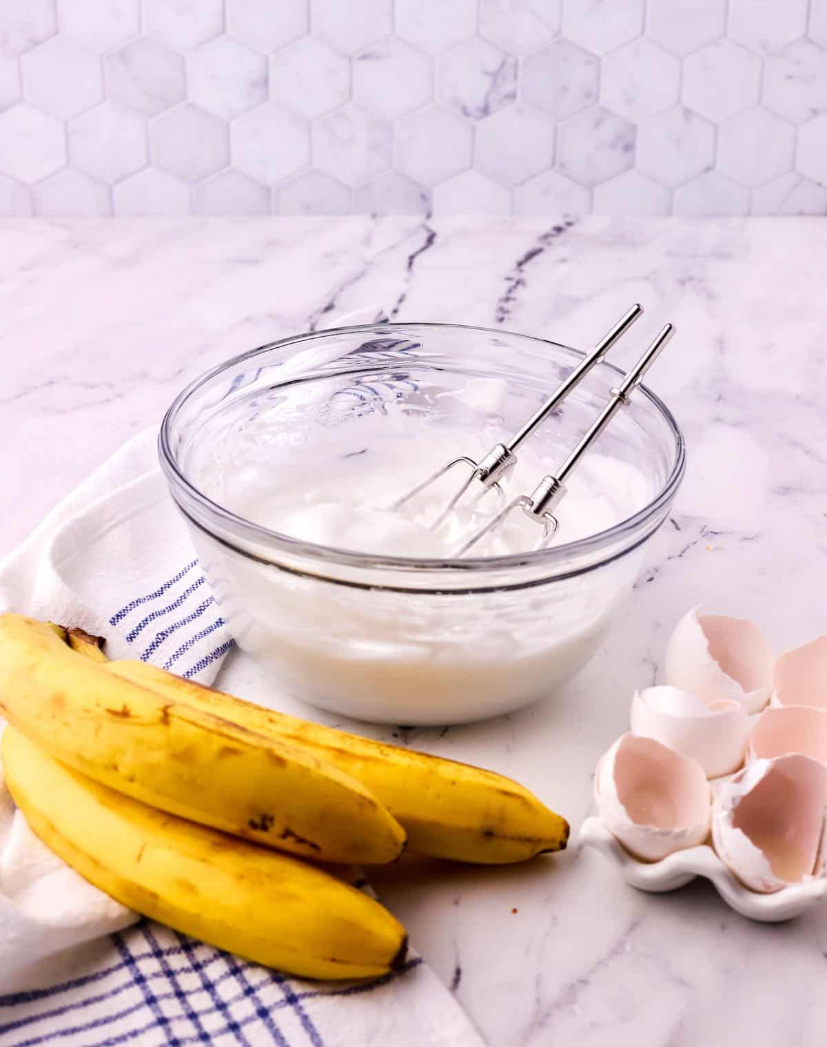 Meringue in a glass bowl with bananas in front.