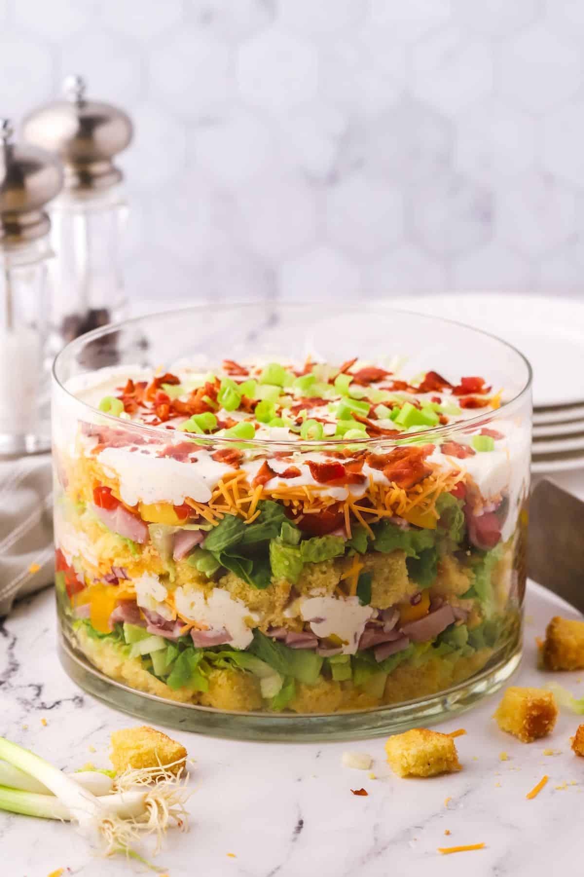 Layered cornbread salad in a trifle dish.