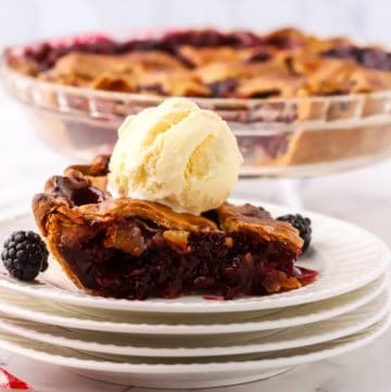 A slice of blackberry pie on a white plate topped with ice cream.
