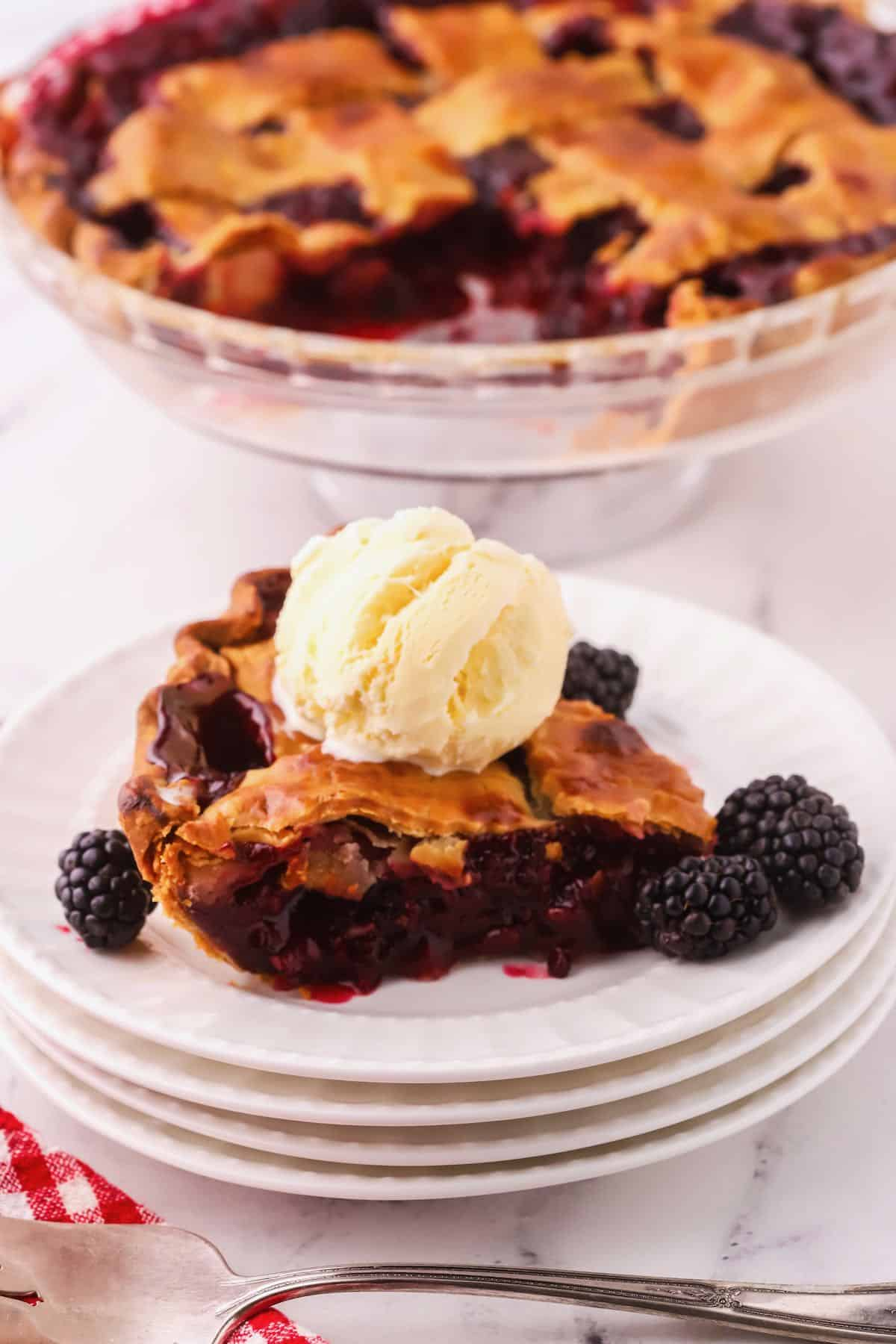 Blackberry pie slice on a plate topped with vanilla ice cream.