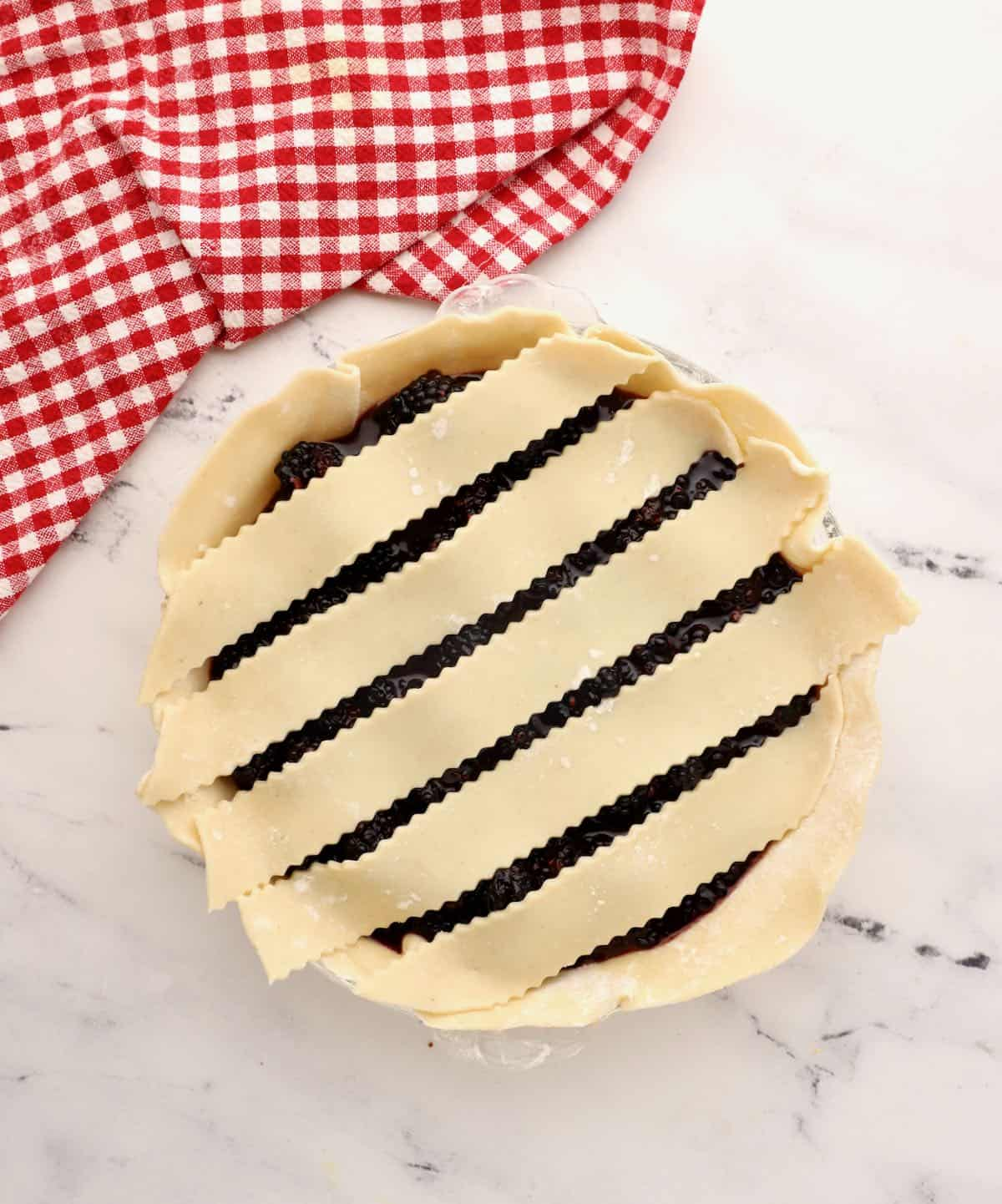 Laying out a lattice crust on a pie.
